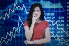 Mujer preocupante con la disminución del gráfico financiero Fotos de archivo