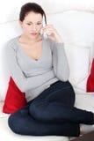 Mujer preocupante en un teléfono. Imagen de archivo libre de regalías