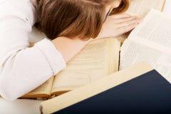 Mujer preocupante joven que duerme en los libros Imagen de archivo libre de regalías