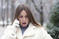 Mujer preocupante joven que llama por teléfono en el parque Foto de archivo