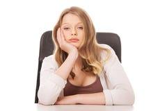 Mujer preocupante joven que se sienta en el escritorio Imagen de archivo