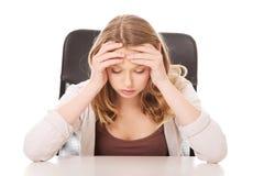 Mujer preocupante joven que se sienta en el escritorio Fotografía de archivo libre de regalías