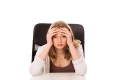 Mujer preocupante joven que se sienta en el escritorio Fotos de archivo libres de regalías