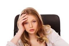 Mujer preocupante joven que se sienta en el escritorio Imágenes de archivo libres de regalías