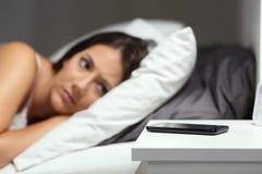 Mujer preocupante que espera una llamada de teléfono en la noche Fotos de archivo libres de regalías
