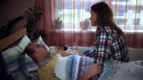 Mujer preocupante que habla con el hombre enfermo enfermo que miente en cama y toser metrajes