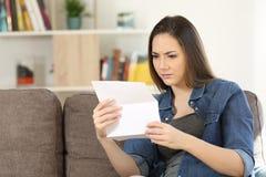 Mujer preocupante que lee una letra en casa Foto de archivo