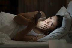 Mujer preocupante que mira el mún contenido en un teléfono del smat en la noche Fotos de archivo
