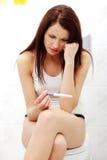 Mujer preocupante que mira la prueba de embarazo. Fotografía de archivo libre de regalías