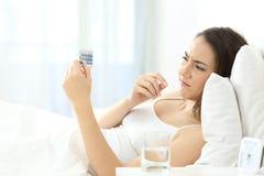 Mujer preocupante que toma una píldora anticonceptiva en la cama Foto de archivo