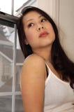Mujer preocupante, triste que mira hacia fuera la ventana Fotografía de archivo
