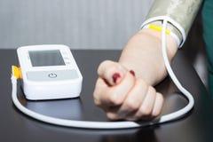 Mujer presión arterial de medición con tonometer misma imagen de archivo