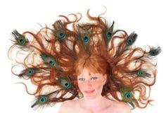 Mujer principal roja con las plumas del pavo real en su pelo Foto de archivo libre de regalías