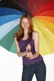Mujer principal roja sonriente con el paraguas del arco iris fotos de archivo