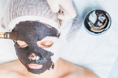 Mujer profesional, cosmetologist en el salón del balneario que aplica la mascarilla del fango Fotografía de archivo