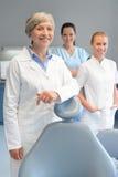Mujer profesional del equipo del dentista en la cirugía dental Imágenes de archivo libres de regalías