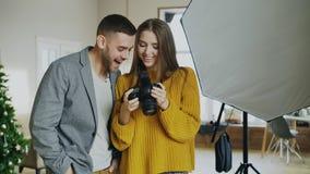 Mujer profesional del fotógrafo que muestra las fotos en la cámara digital al hombre modelo atractivo en estudio de la foto dentr imágenes de archivo libres de regalías