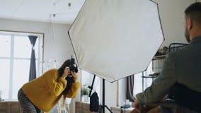 Mujer profesional del fotógrafo que toma la foto de la muchacha del modelo del hombre de negocios con la cámara digital en estudi fotografía de archivo libre de regalías