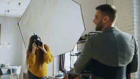 Mujer profesional del fotógrafo que toma la foto de la muchacha del modelo del hombre de negocios con la cámara digital en estudi imágenes de archivo libres de regalías