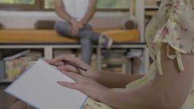 Mujer profesional del psicólogo que consulta al paciente masculino joven y que toma notas durante la sesión de terapia en su ofic metrajes