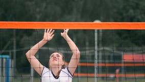 Mujer profesional del servicio del voleibol en el torneo de la playa La red del voleibol el jugador bloquea la visión al aplicars almacen de metraje de vídeo