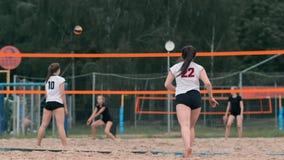 Mujer profesional del servicio del voleibol en el torneo de la playa La red del voleibol el jugador bloquea la visión al aplicars almacen de video