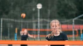 Mujer profesional del servicio del voleibol en el torneo de la playa La red del voleibol el jugador bloquea la visión al aplicars metrajes