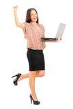 Mujer profesional feliz que sostiene una computadora portátil Imágenes de archivo libres de regalías