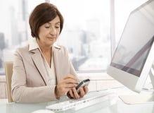 Mujer profesional mayor que usa pda en oficina Imágenes de archivo libres de regalías