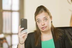 Mujer profesional que reacciona al contenido del teléfono Fotografía de archivo libre de regalías