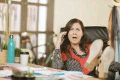 Mujer profesional que reacciona a la conversación telefónica Foto de archivo