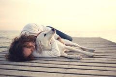 Mujer protectora que abraza su perro mientras que duerme imagenes de archivo