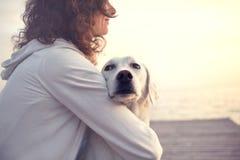 Mujer protectora que abraza su perro mientras que mira la visión imágenes de archivo libres de regalías
