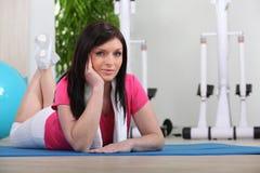 Mujer puesta en la estera del gimnasio Fotos de archivo libres de regalías