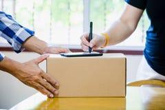 Mujer que añade la muestra de la firma en el smartphone para enviar las cajas con el hombre del poste en la oficina de correos imágenes de archivo libres de regalías