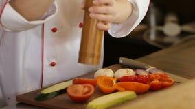 Mujer que añade la sal a la ensalada vegetal, primer almacen de video