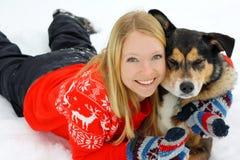 Mujer que abraza al pastor alemán Dog en nieve Imágenes de archivo libres de regalías