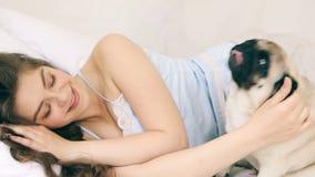 Mujer que abraza con el perro del barro amasado en cama Imágenes de vídeo, momento soleado relajado de la mañana Familia del amor metrajes