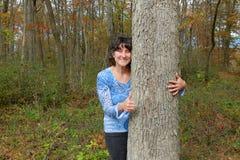 Mujer que abraza el árbol Imágenes de archivo libres de regalías