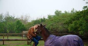 Mujer que abraza el caballo en la cerca de madera 4k almacen de metraje de vídeo