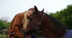 Mujer que abraza el caballo en la cerca de madera en el rancho 4k almacen de metraje de vídeo