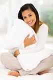 Mujer que abraza la almohadilla Fotografía de archivo