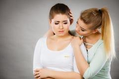 Mujer que abraza a su amigo femenino triste Imagen de archivo libre de regalías
