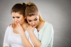 Mujer que abraza a su amigo femenino triste Imagen de archivo
