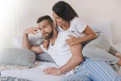 Mujer que abraza a su novio ofendido mientras que miente en cama Foto de archivo libre de regalías