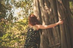 Mujer que abraza un árbol gigante Foto de archivo libre de regalías