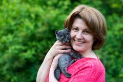 Mujer que abraza un estrecho escocés del gatito azul adentro al aire libre imagen de archivo