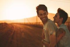 Mujer que abraza a un hombre al aire libre en un viaje por carretera Fotos de archivo libres de regalías