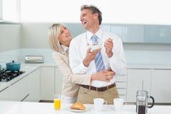 Mujer que abraza a un hombre feliz de detrás en cocina Imagen de archivo libre de regalías