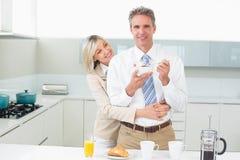 Mujer que abraza a un hombre feliz de detrás en cocina Fotografía de archivo libre de regalías